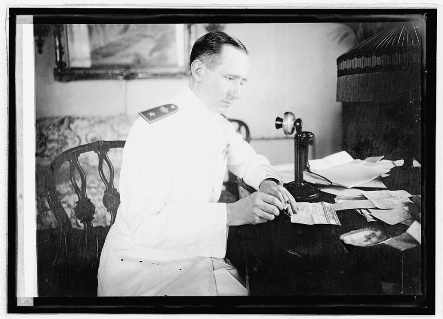A photo of Guglielmo Marconi seated with a telephone in hand.