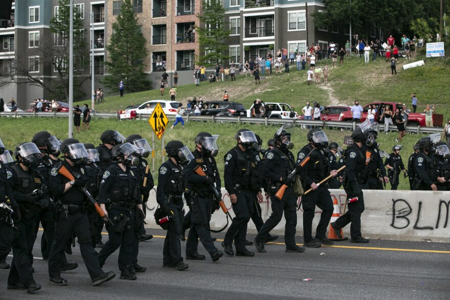 A line of Austin police officers move toward protesters on Interstate 35 on May 31.