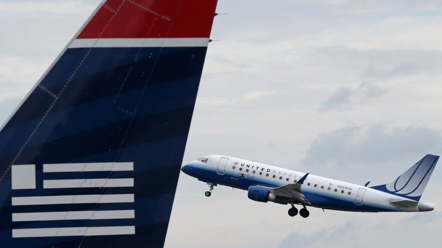 A United Airlines jet takes off behind a US Airways jet at Ronald Reagan Washington National Airport on Tuesday.
