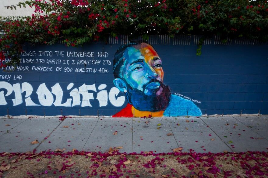 A mural of Nipsey Hussle is ringed by flowers on Brynhurst Ave. in Crenshaw Dec. 5, 2020. In the wake of Nipsey Hussle's March 2019 death, many murals of the beloved Los Angeles musician were painted in the Hyde Park neighborhood near his Marathon clothing store. The store and a large Nipsey mural in its alleyway is now fenced off but other nearby murals continue to draw local and visiting fans.