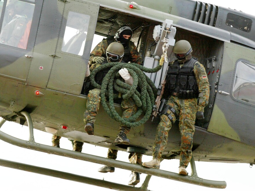Soldiers of the Command Special Forces (KSK) of the Bundeswehr are preparing to rappel from a helicopter during an exercise in 2004.