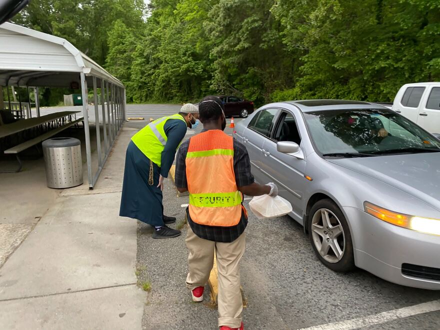 Islamic Center of Charlotte's Imam Muhammad Khan and a volunteer hand out meals to a family