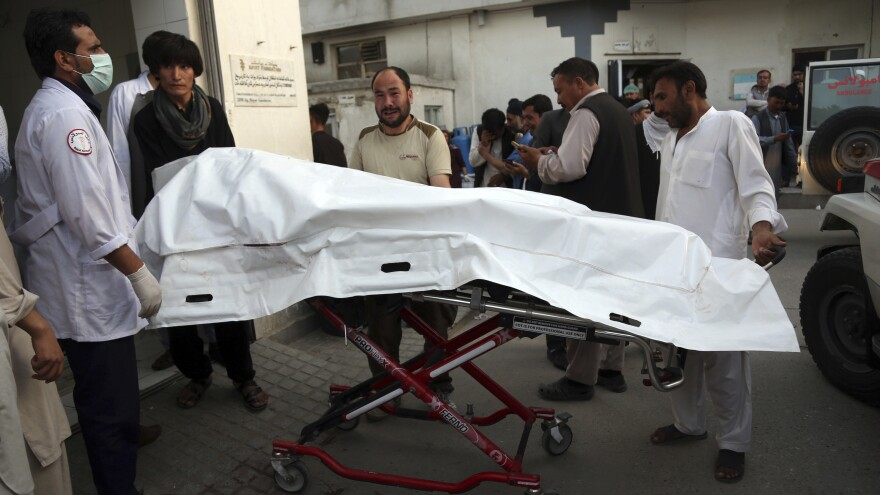 Afghans carry the body of a man who was killed in a deadly suicide bombing that targeted an educational center in the Shiite neighborhood of Dasht-i Barcha, in western Kabul, Afghanistan, on Wednesday.