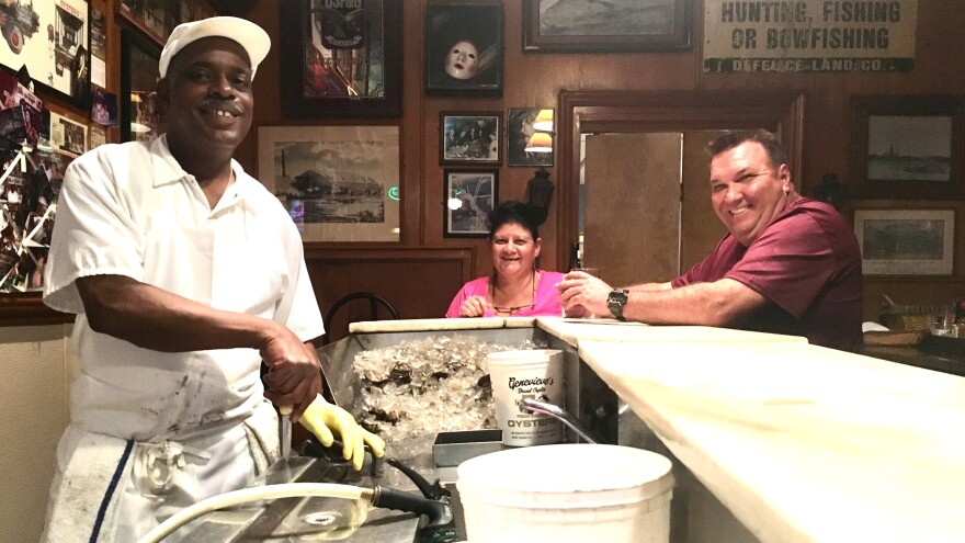 "<a href=""http://mediad.publicbroadcasting.net/p/wwno/files/styles/x_large/public/201811/img-6038_1__1.jpg""> </a> Thomas ""Uptown T"" Stewart (left), has been shucking oysters at Pascal's Manale restaurant for more than 30 years, about as long as Paula (middle) and Brent Coussou have been going there."