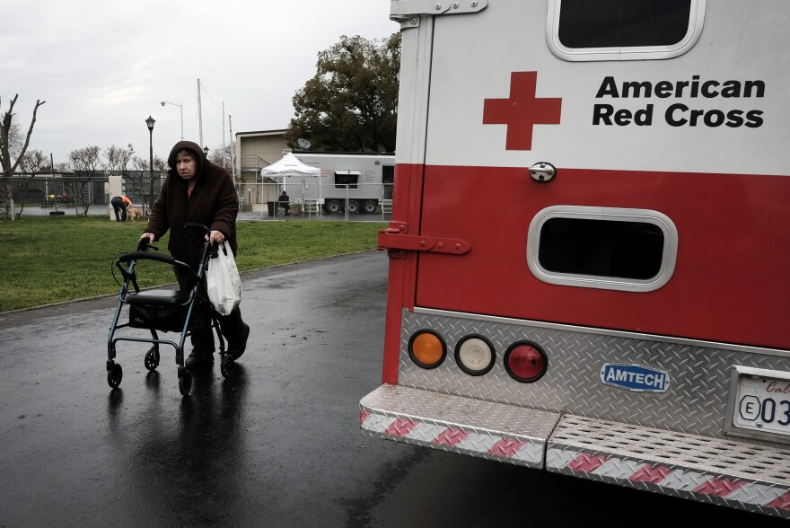 An evacuee walks past an American Red Cross vehicle at an evacuation center in Chico, Calif., on Feb. 15, 2017. Flooding had damaged the nearby Oroville Dam and there was danger it might break. Around 188,000 people were evacuated, but the dam held.