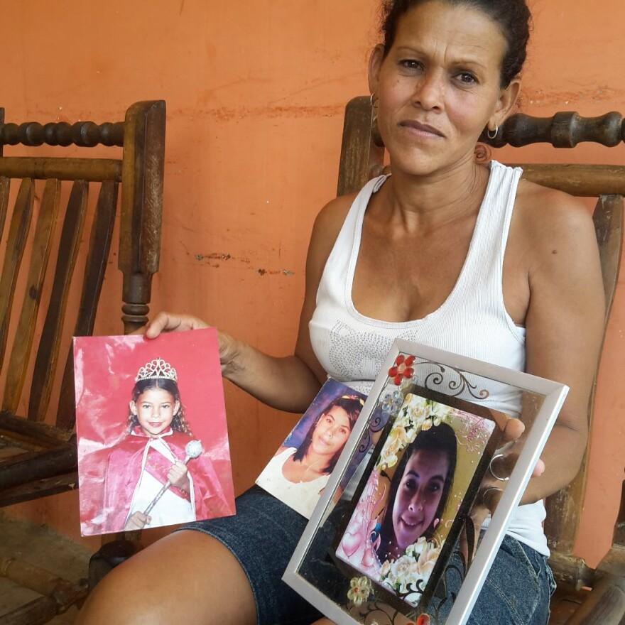 Venezuelan Auri Chirinos holds photos of her daughter, Jeanauri Jiménez Chirinos, who died trying to get to Curaçao.