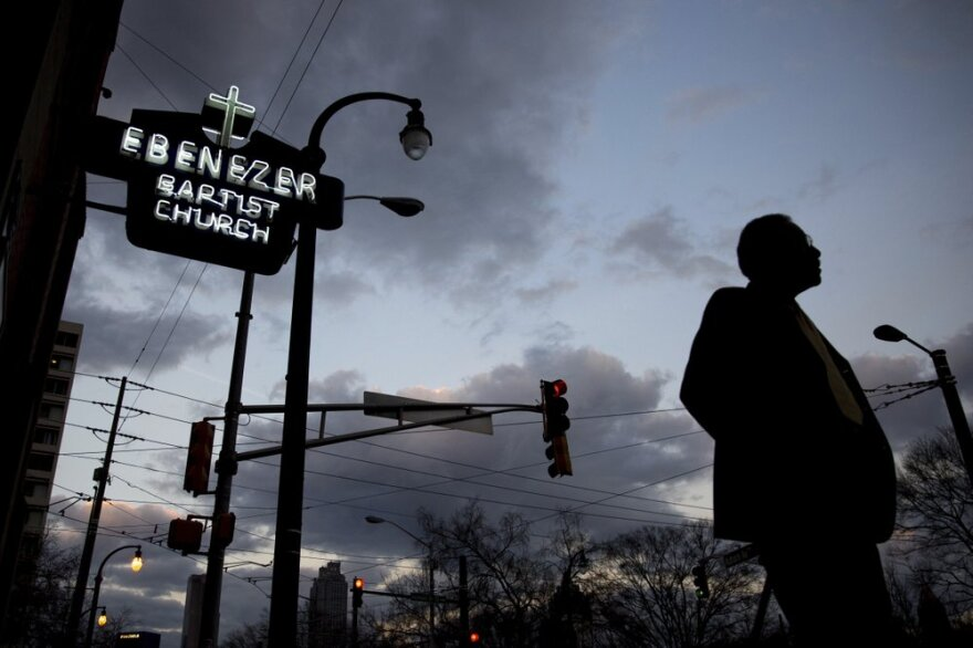 A man in shadow stands outside Ebenezer Baptist Church in Atlanta, Georgia. As the sunrise begins to light the sky, the historic church's neon sign is lit.