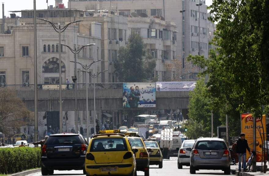 Syrians drive past government billboards in the capital of Damascus on Saturday, as a partial cease-fire — the first major truce of the five-year war — takes hold. Guns fell silent at midnight in suburbs around the capital and the bomb-scarred northern city of Aleppo.