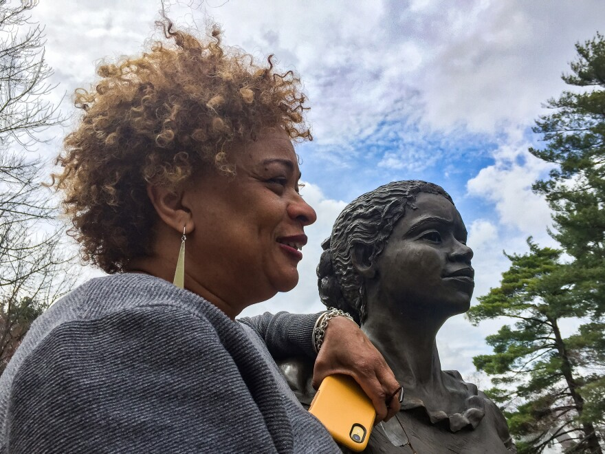 JerriAnne Boggis, executive director of the Black Heritage Trail of New Hampshire, poses with a monument that was erected in Harriet E. Wilson's honor. Boggis says when she read Wilson's book, she felt as if it was written the book just for her.