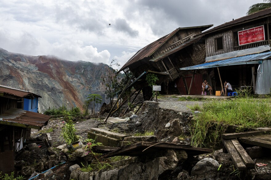 Residents sit near a damaged house caused by a landslide at a mining site in Hpakant in July. The landslide killed nearly 200 people.