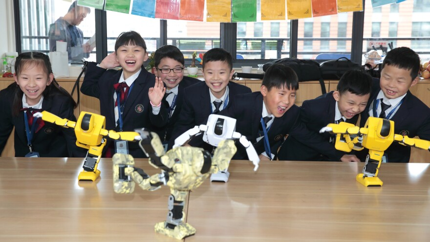 Students at Hailiang Foreign Language School in Zhuji watch robots performing in a class in March. The operator of the school, Hailiang, saw its stock price reach unprecedented — and erroneous — heights Thursday.