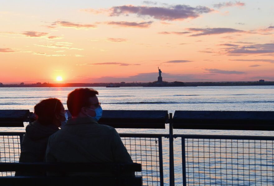 A couple watches the sunset on April 28, 2020 in New York City. (Angela Weiss/AFP via Getty Images)