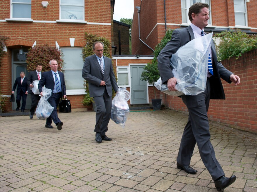 Investigators carry bags of evidence from the home of Andy Coulson, a former <em>News of the World</em> editor and Cameron aide, in London on Friday. Police arrested Coulson in the phone hacking scandal.