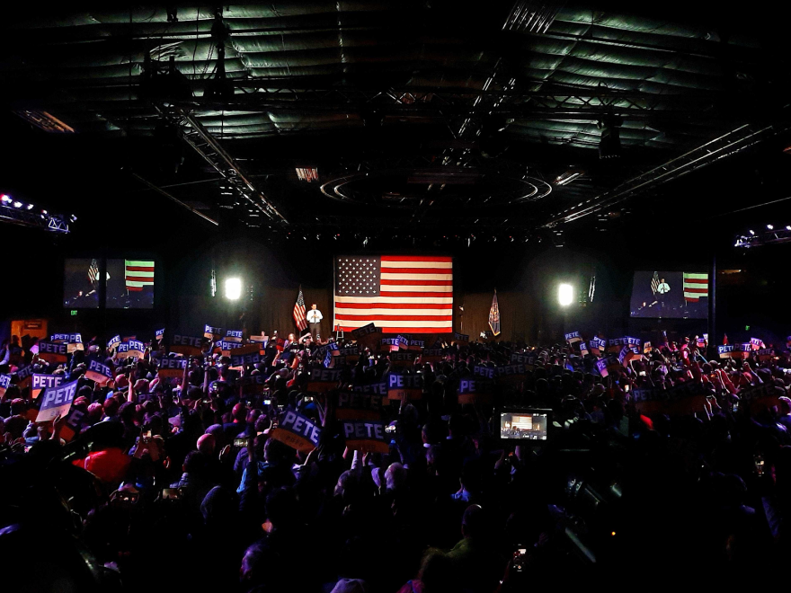 Photo of a room crowded with people holding campaign signs and listening to pete buttigeig speak on a stage in front of an American flag