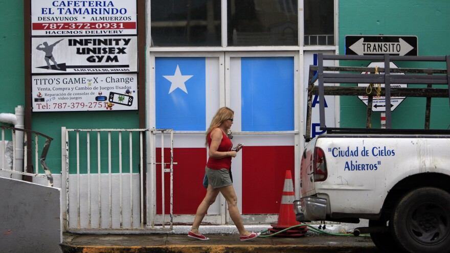 A woman walks in front of a business with the municipal flag painted on the entrance doors in Lares, Puerto Rico, on Sept. 2, 2015. Puerto Rico's economy has been struggling, and Puerto Ricans living on the U.S. mainland, who can vote, vow to be heard this election in an effort to help the ailing U.S. territory.