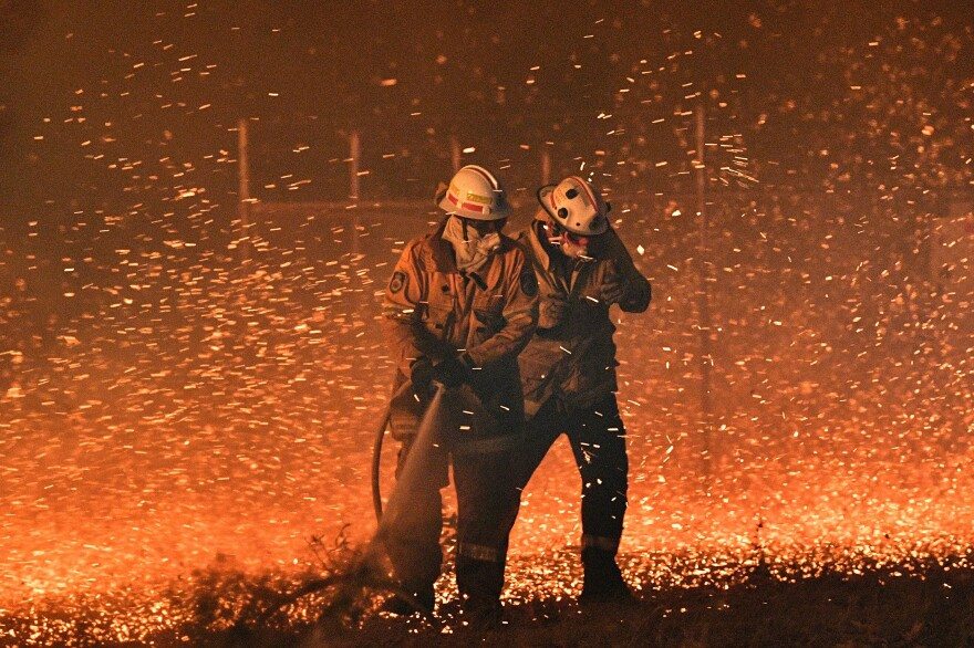 Firefighters struggle to protect homes from the embers generated by bushfires near the town of Nowra in New South Wales, Australia.