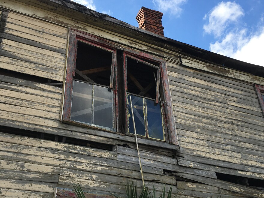 A close up of the house showing rotten wood, peeling paint and broken windows.