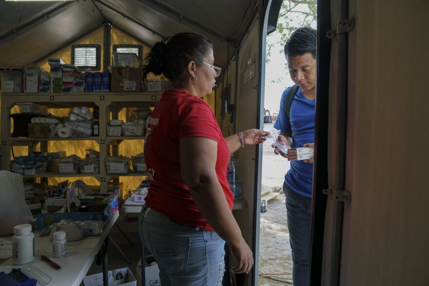 Perla, an asylum-seeker who works at the Global Response Management clinic gives a patient his medication in a migrant camp in Matamoros, Mexico on March 17, 2020.