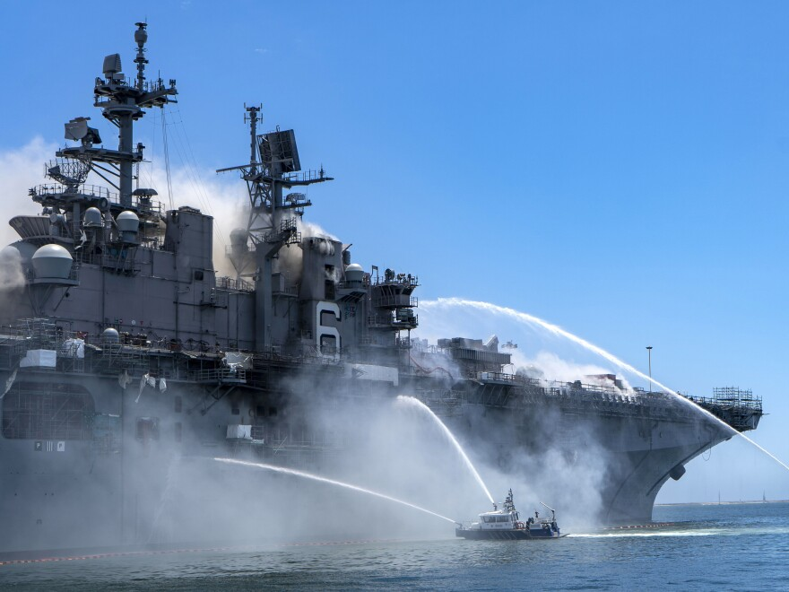 Police boats combat a fire aboard the amphibious assault ship USS Bonhomme Richard at Naval Base San Diego on Sunday.