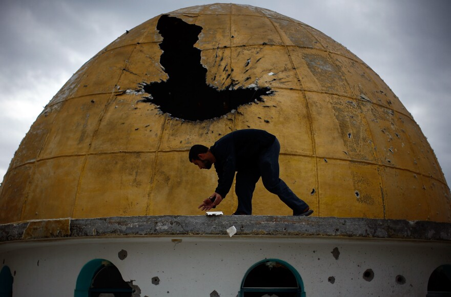A Palestinian man picks up fragments of a mosque's golden dome, which was hit by a tank round during the fighting between Hamas and Israeli forces, north of Gaza City on Jan. 20, 2009.