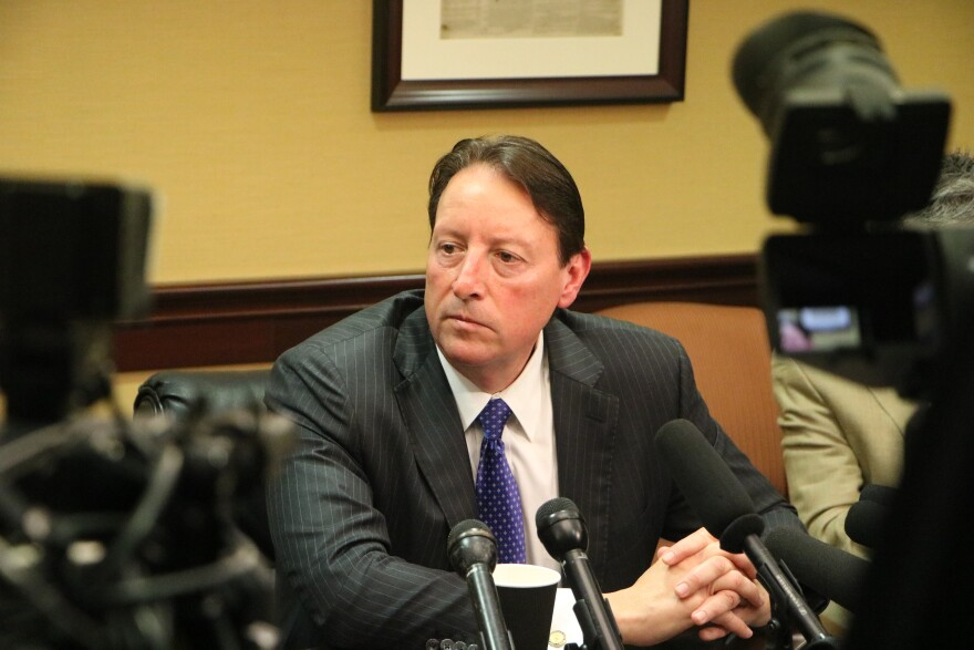 A man in a dark suit, white shirt and blue tie sits at a table surrounded by microphones