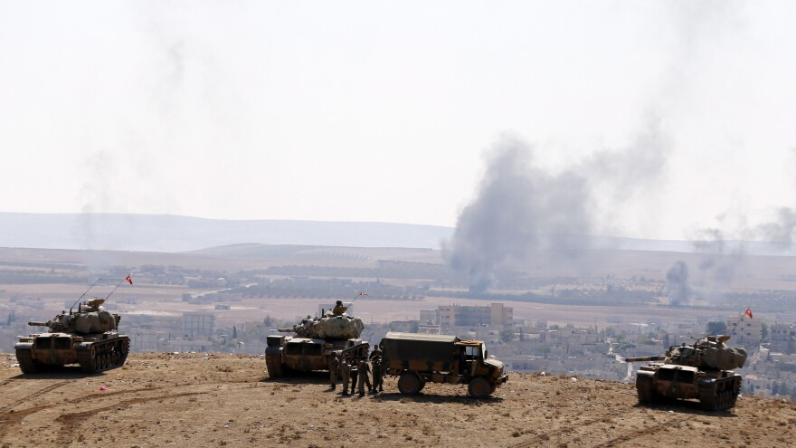 Smoke rises from the Syrian town of Kobani as Turkish army tanks take up position on the Turkish side of the border, as seen from near the Mursitpinar border crossing on the Turkey-Syria border Wednesday.