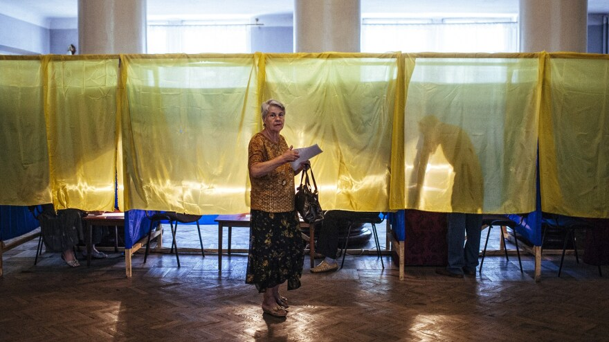 A woman holds her ballot in a polling station in the eastern Ukrainian town of Dobropillya.