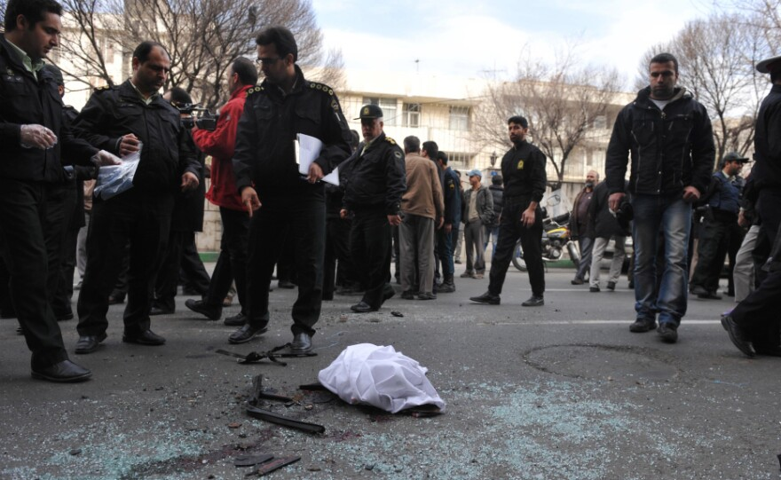 Iranian security forces inspect the site where a magnetic bomb attached to a car by a motorcyclist exploded outside a university in Tehran on Wednesday, killing nuclear scientist Mostafa Ahmadi Roshan.