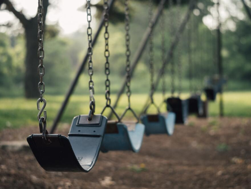 a row of emtpy swings in the park with trees in the background