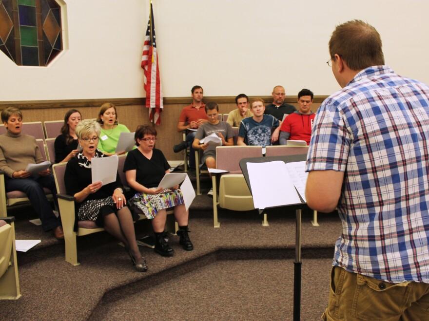 The choir's musical director, Bryan Horn, leads the ensemble in rehearsal.