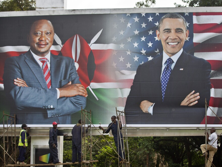 Workers finish installing a billboard showing Kenya's President Uhuru Kenyatta and President Barack Obama in downtown Nairobi a day before Obama's visit.