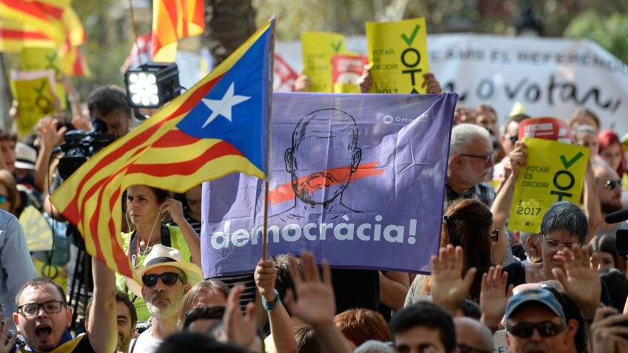 """People hold Catalan pro-independence flags outside the high court in Barcelona, Spain, on Thursday. After a daylong protest that lasted well into the night, several thousand independence supporters gathered again in front of the high court in what influential separatist organizations said would be a """"permanent mobilization"""" until detained Catalan officials are freed."""