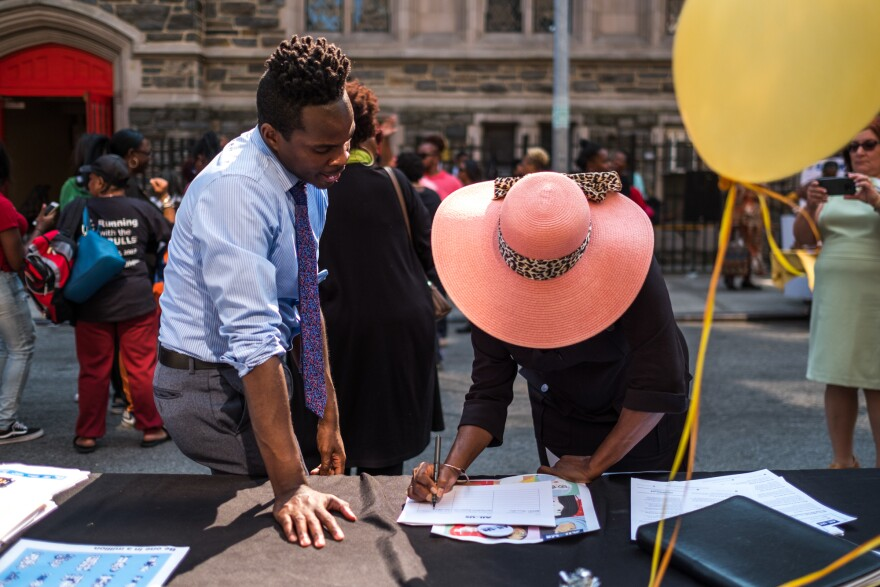 Kolbi Brown (left), a program manager at Harlem Hospital in New York, helps Karen Phillips sign up to receive more information about the All of Us medical research program, during a block party outside the Abyssinian Baptist Church in Harlem.
