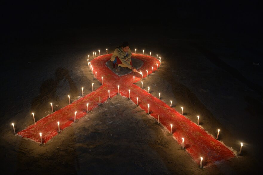 An Indian sex worker lights candles forming the shape of a ribbon as part of an awareness event on the occasion of World AIDS Day in Siliguri on December 1, 2018. - World AIDS Day has been observed today since 1988 to raise awareness of the AIDS pandemic. (Diptendu Dutta/AFP via Getty Images)