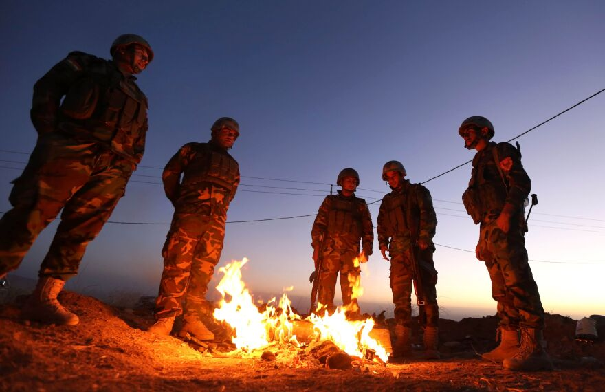 Iraqi Kurdish Peshmerga fighters stand next to a fire as they gather on the top of Mount Zardak, about 25 kilometres east of Mosul, on Monday.