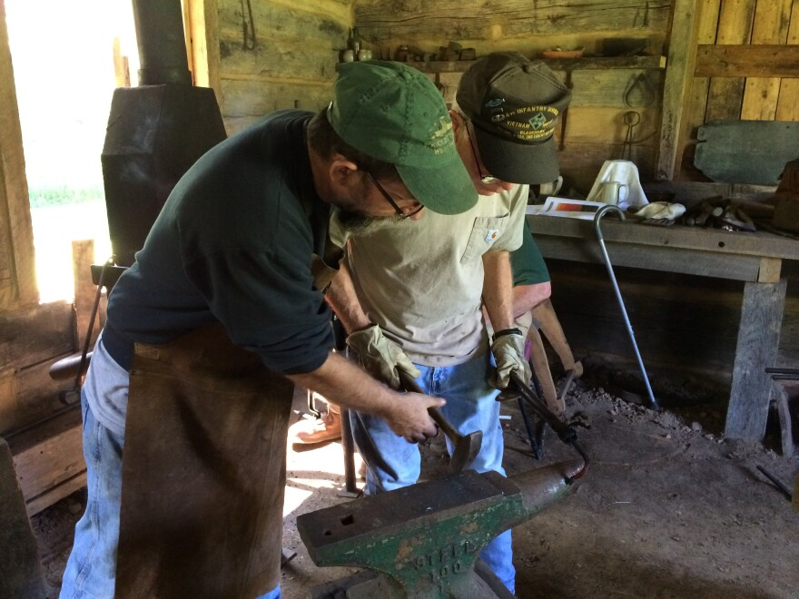 Greg Bray shows Chuck Huff a technique during a blacksmithing workshop at Pricketts Fort State Park.
