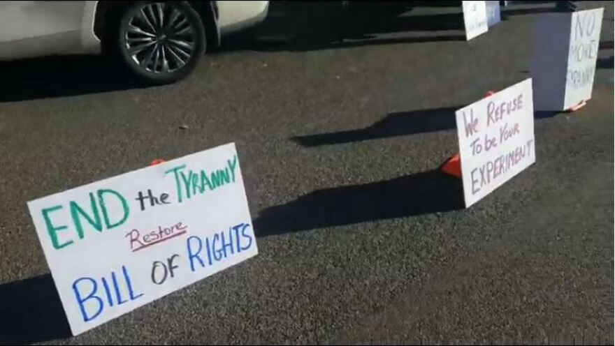 """Handwritten signs propped up on the ground read """"End the tyranny, restore Bill of Rights"""" and """"We refuse to be your experiment."""""""