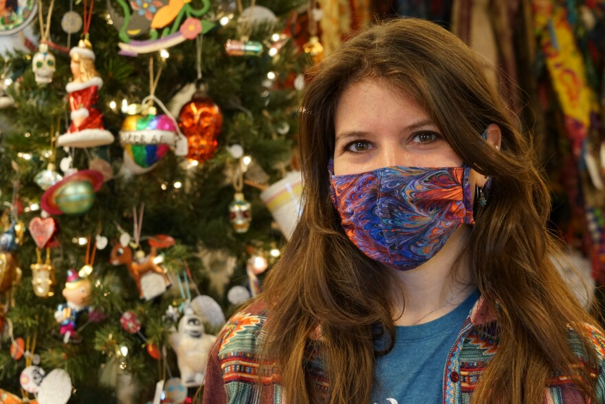 A young woman wears a colorful face mask. She stands in front of a Christmas tree.