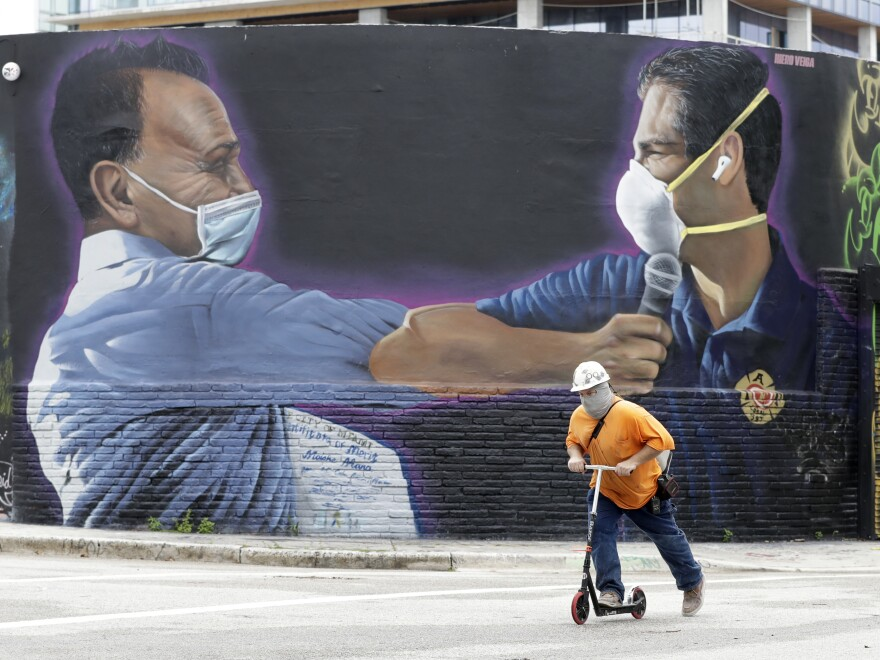 A construction worker rides a scooter Monday in Miami past a Hiero Veiga mural of businessman Moishe Mana (left) and Miami Mayor Francis X. Suarez wearing masks.