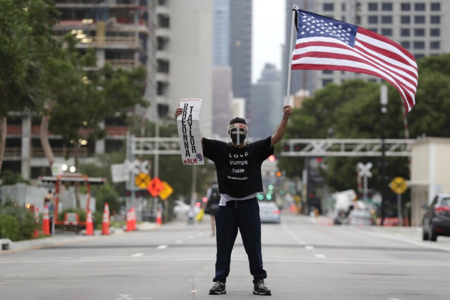 Freddie Peralta holds a sign in memory of Breonna Taylor during a protest over the death of George Floyd and others, Saturday, June 6, 2020, in downtown Miami. He is wearing a mask and face shield amid the COVID-19 pandemic.