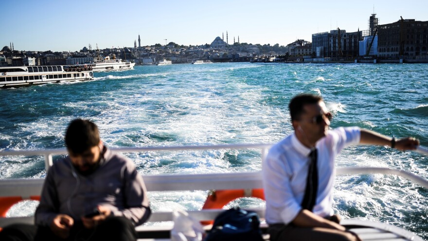 People travel on the Bosphorus by ferry through Istanbul on Wednesday. A bloom of phytoplankton has turned the strait bright turquoise.
