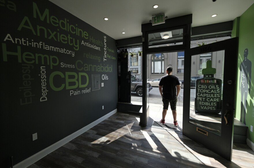 In this photo taken Thursday, March 21, 2019, Gus Dabais stands in the entry to his Sidewalk Wellness store in San Francisco.