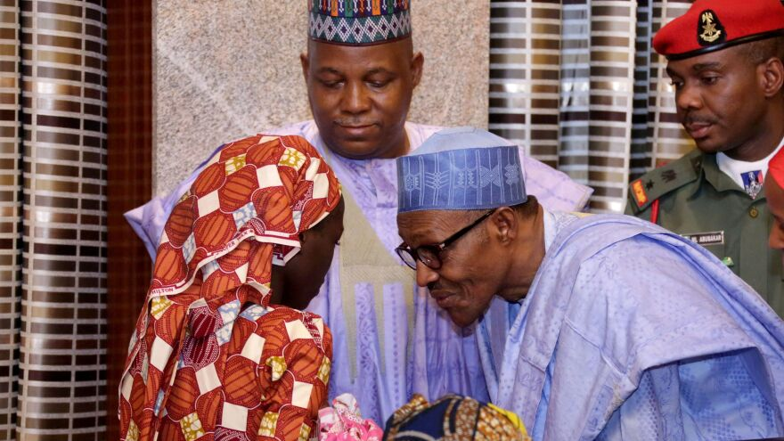 Nigerian president Muhammadu Buhari speaks with Chibok schoolgirl Amina Ali Nkeki, who was freed on May 19. She is carrying her baby. Borno state governor Kashim Shettima (center) looks on.