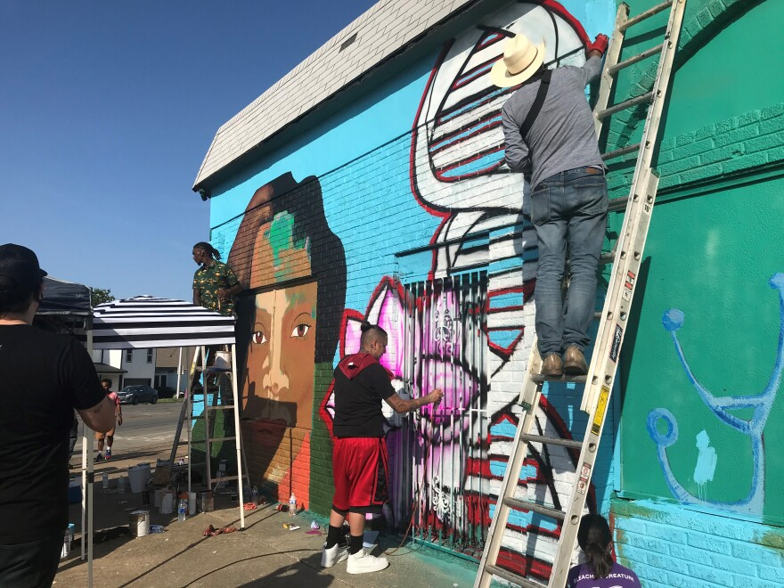 Three people on ladders work on a colorful mural, featuring Atatiana Jefferson's face, a pink flower, and a strand of DNA.