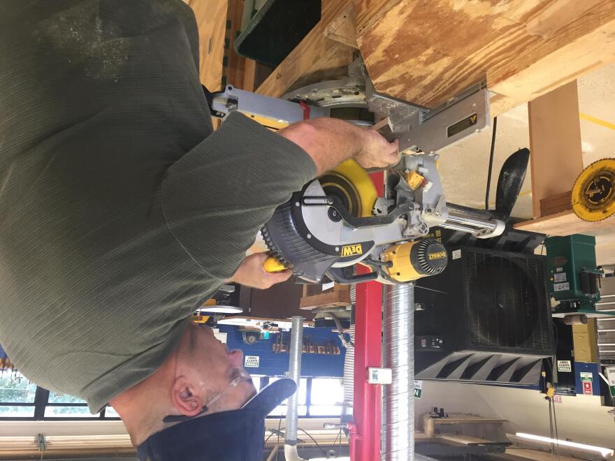 A man operates a circular saw in a wood shop