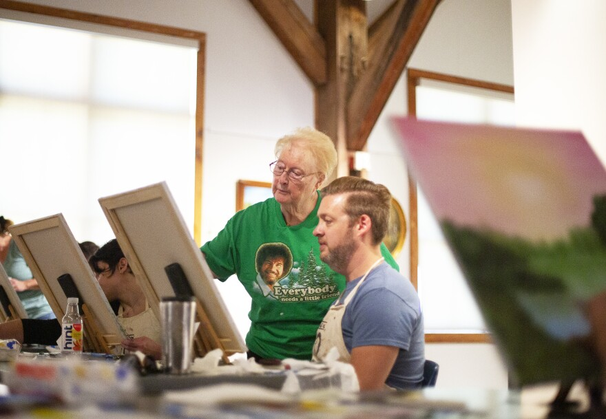 Sandra Hill offers guidance to Mark Scheiffley during a Bob Ross painting class at the Franklin Parks Art Center in Purcellville, Va., on Sept. 20. Hill is one of more than 3,000 people certified to teach the Bob Ross wet-on-wet painting technique.
