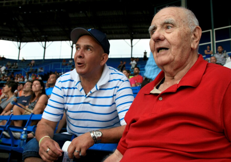 Ismael Sené (right), a former intelligence agent-turned-baseball historian, watches a game at Latin American Stadium.