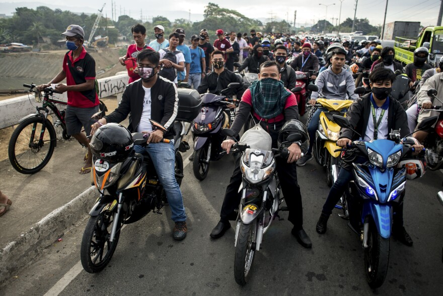 Motorcyclists pile up at a control point in Manila on March 16, when a community quarantine was mandated to curb the spread of COVID-19. Police officers and soldiers monitor entry and exit from the capital region.