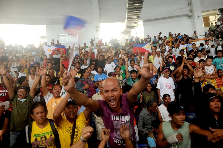 Sunday, Typhoon survivors watch the boxing match between Philippine hero Manny Pacquiao and American boxer Brandon Rios at the Tacloban Convention Center, which had been used as an evacuation center.
