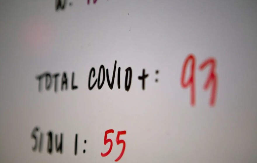 A whiteboard showing COVID case numbers.
